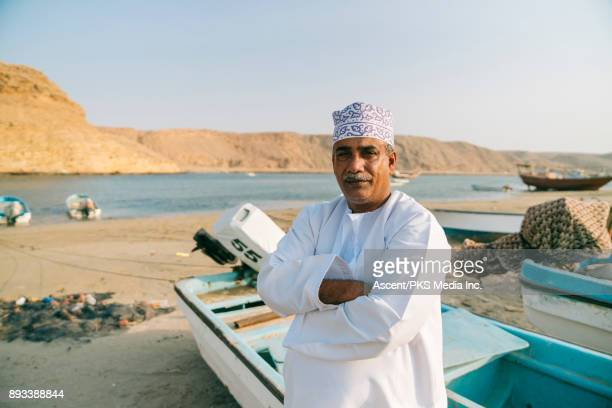 Middle Eastern man stands in front of small boats at port