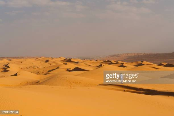 middle eastern man stands on dunes in desert - mid distance stock pictures, royalty-free photos & images
