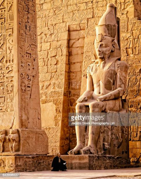 middle eastern man under ancient statue, luxor, egypt - egypt stock pictures, royalty-free photos & images