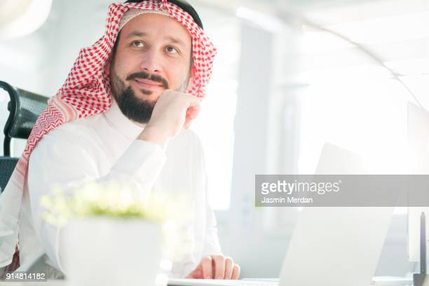 middle eastern man using computer for professional work - back lit stock pictures, royalty-free photos & images