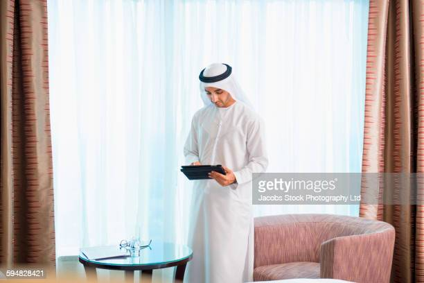 Middle Eastern man using digital tablet in hotel room