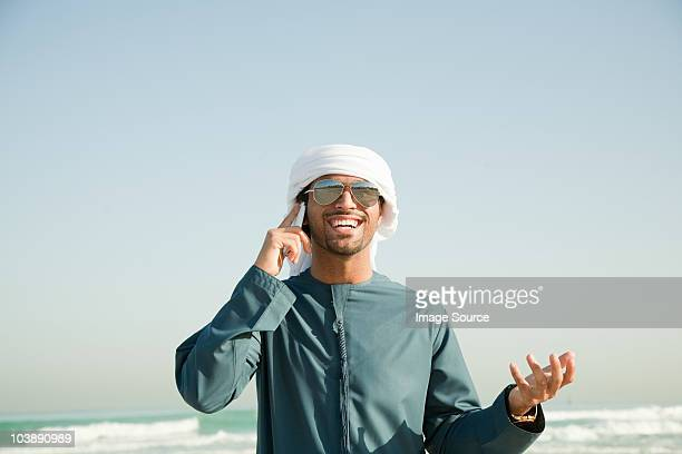 Middle Eastern man using mobile phone on the beach