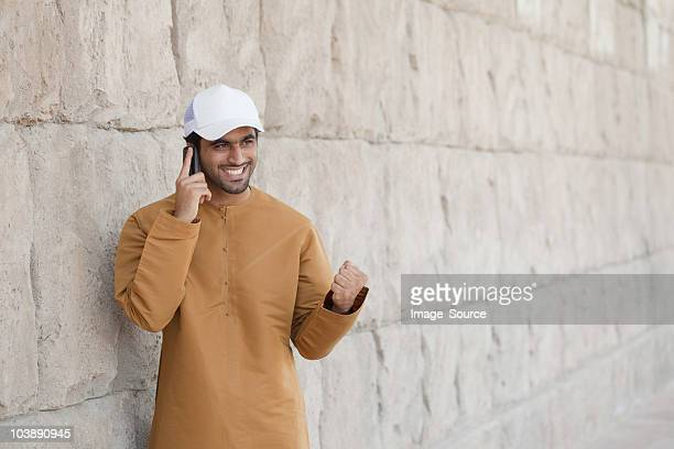 middle eastern man using mobile phone - baseball cap stock pictures, royalty-free photos & images