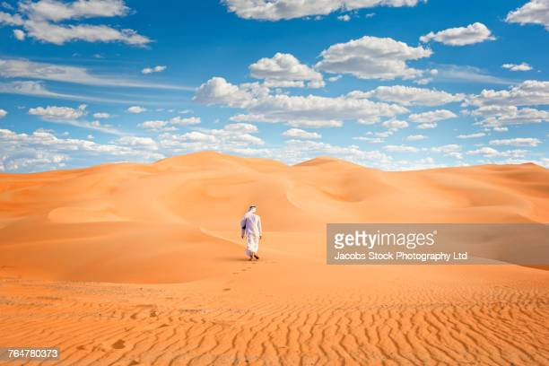 middle eastern man walking in desert - sand dune stock pictures, royalty-free photos & images