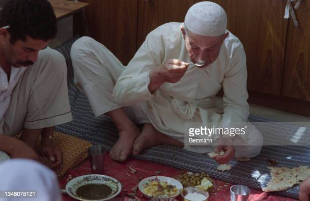 Middle Eastern man wearing a kufi, eating from a spoon with bowls of food arranged on a blanket before him, a second man sitting to the left of the...