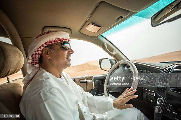 Middle eastern man wearing traditional clothes driving off road vehicle in desert, Dubai, United Arab Emirates