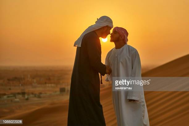 middle eastern men greeting in a traditional arab culture in desert at sunrise - abu dhabi stock pictures, royalty-free photos & images