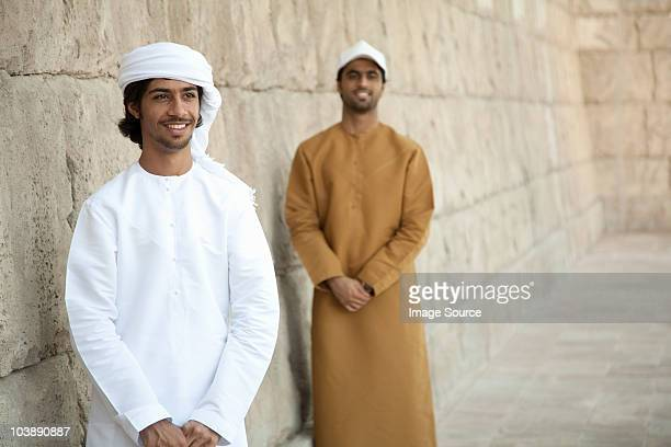 Middle Eastern men looking at by stone wall