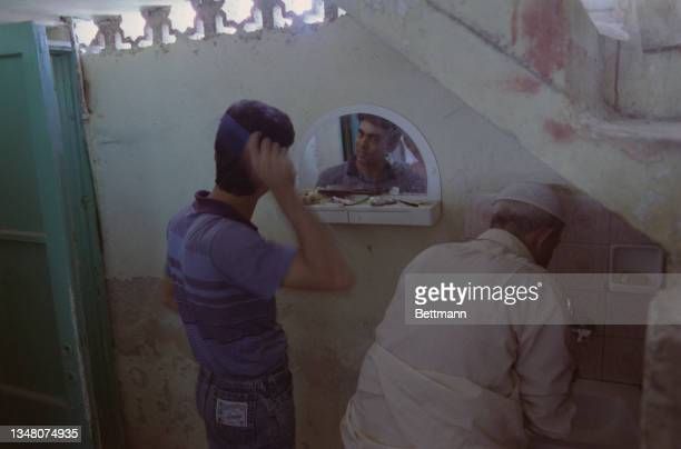 Middle Eastern men, one uses a mirror to comb his hair, the other wears a kufi as he leans over a sink in a bathroom in an unspecified area of...
