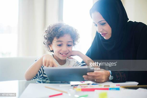 Middle eastern mother helping her child with homework.