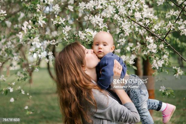 Middle eastern mother kissing son under flowering tree