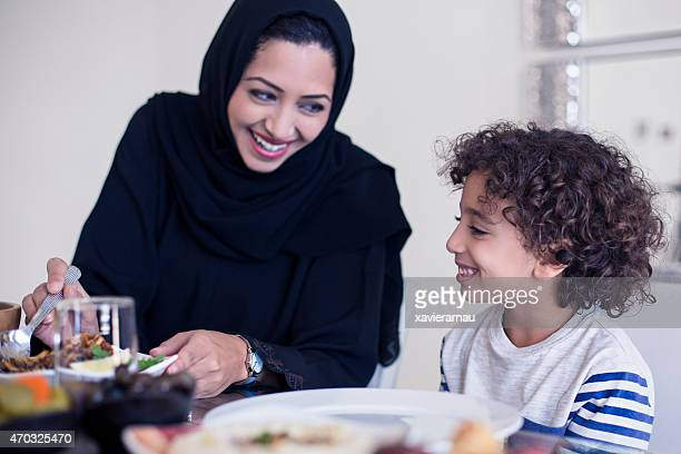 Middle Eastern mother serving food to her son