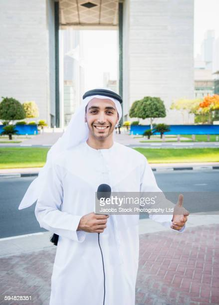 Middle Eastern news anchor talking with microphone