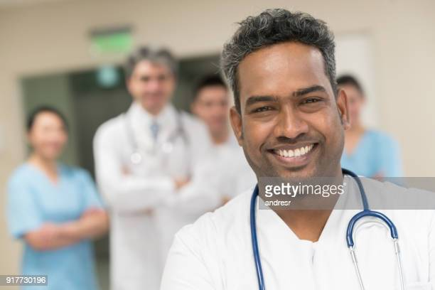 Middle eastern nurse smiling at the camera and a team of physicians standing at the background smiling