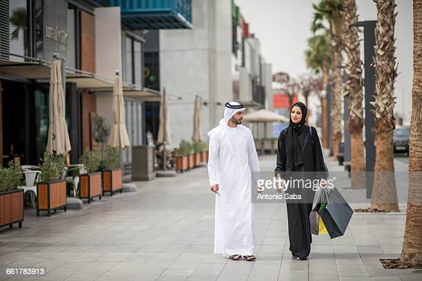 middle eastern shopping couple wearing traditional clothing carrying shopping bags, dubai, united arab emirates - shopping stock pictures, royalty-free photos & images