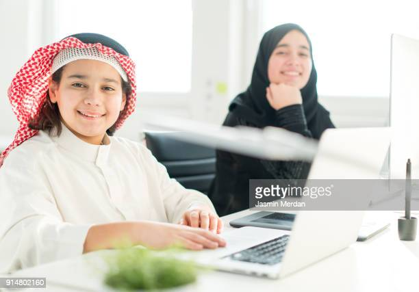 Middle Eastern students learning computer programming on laptops