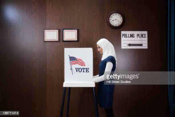 middle eastern voter voting in polling place - votes for women stock photos and pictures