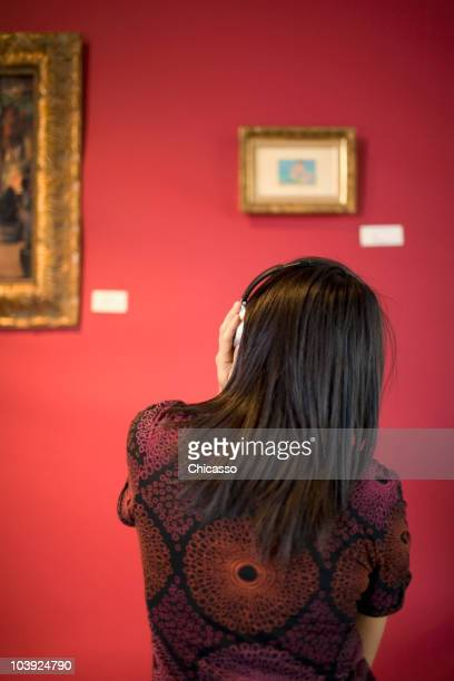 Middle Eastern woman admiring painting in museum