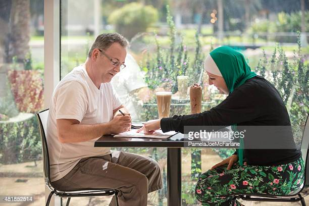 Middle Eastern Woman and Caucasian Man Doing Business in Café