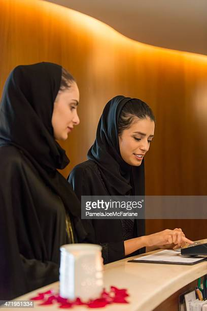 Middle Eastern Woman at Counter Paying by Credit Debit Reader
