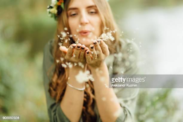 Middle Eastern woman blowing dandelion seeds