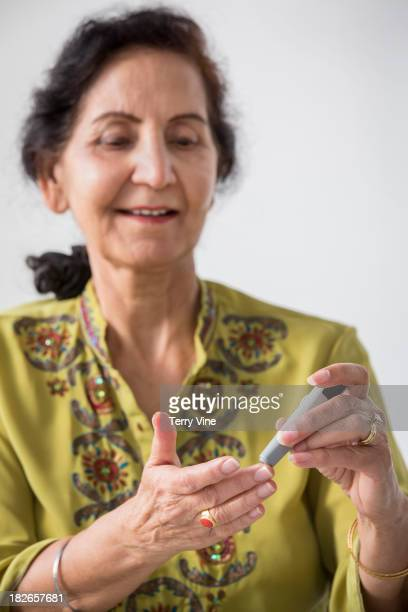 Middle Eastern woman checking her blood sugar