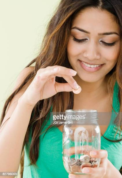 Middle Eastern woman dropping coins in jar