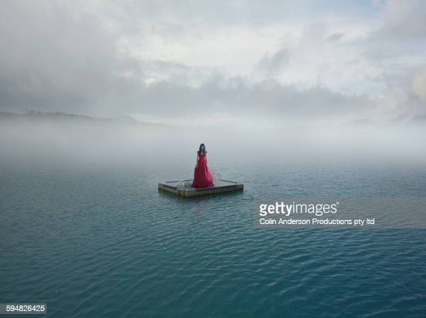 middle eastern woman floating on dock in remote lake - stranded stock photos and pictures