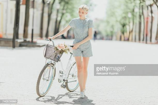 middle eastern woman holding bouquet and walking bicycle - montare foto e immagini stock
