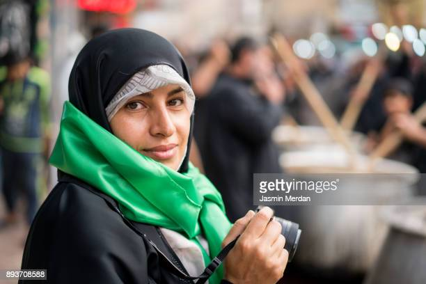 middle eastern woman on the street using camera for taking images - hajj photos et images de collection