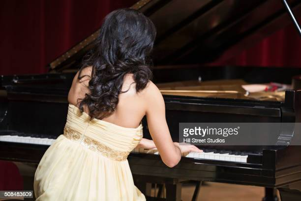 Middle Eastern woman playing piano