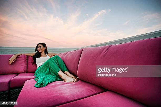 Middle Eastern woman relaxing on sofa outdoors