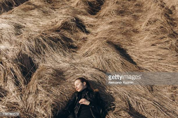 Middle Eastern woman resting in tall grass