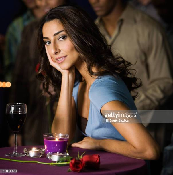 middle eastern woman sitting at nightclub table - impatience flowers stock pictures, royalty-free photos & images