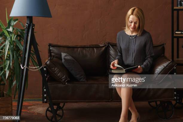 Middle Eastern woman sitting on sofa reading book