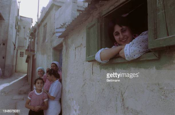 Middle Eastern woman smiling at a small window, in the background a group of Middle Eastern women and children standing by a doorway outside a...