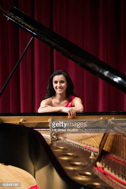 middle eastern woman smiling at piano - pianist front stock pictures, royalty-free photos & images