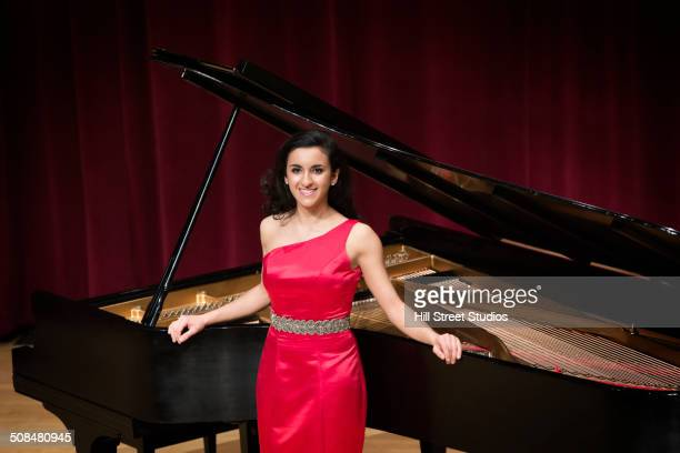 middle eastern woman standing at piano - pianist front stock pictures, royalty-free photos & images