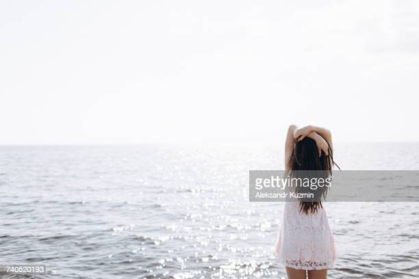 Middle Eastern woman standing near ocean