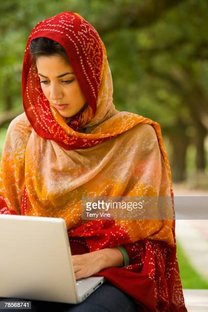 Middle Eastern woman typing on laptop
