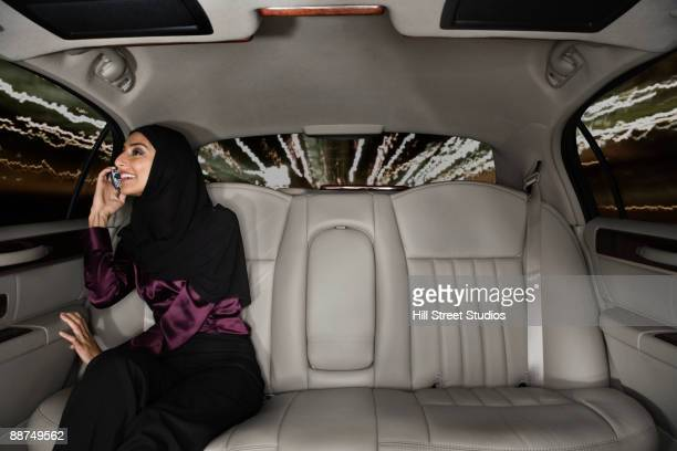 Middle Eastern woman using cell phone in car