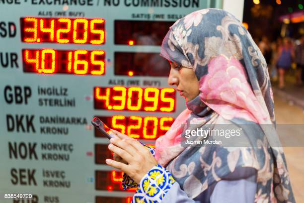 Middle Eastern woman using phone for checking currency