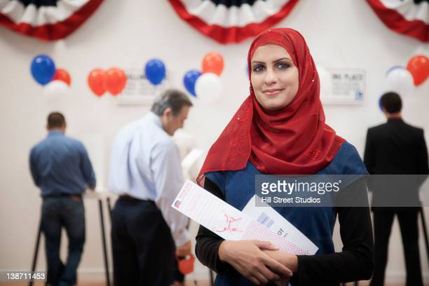 Middle Eastern woman waiting to vote in polling place