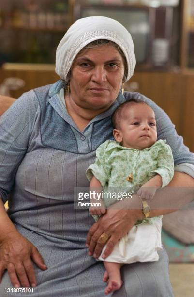 Middle Eastern woman wearing a headscarf and a blue dress, holding a baby dressed in green-and-white clothing, an unspecified area of the West Bank,...