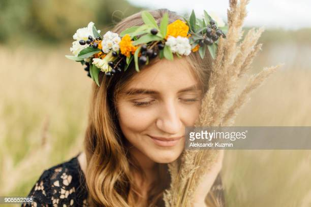 Middle Eastern woman wearing flower crown holding wheat to face