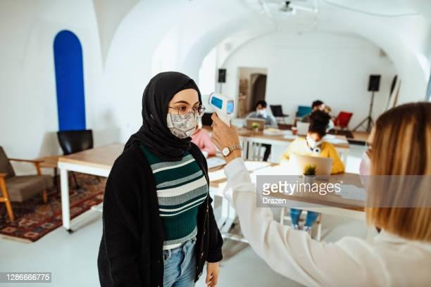 femme du moyen-orient avec le hijab dans le bureau, vérifiant la température avec le thermomètre infrarouge - hijab feet photos et images de collection