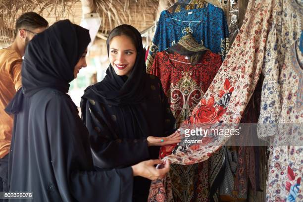 Middle eastern women checking out displayed dress