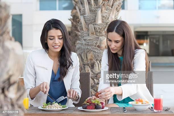 Middle Eastern Frauen Freunde Essen und vegetarische Mittagessen im Café im Freien