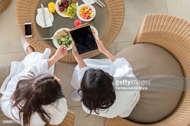 Mitte Östliche Frauen Freunde überprüfen Tablet PC im Spa-Mittagessen