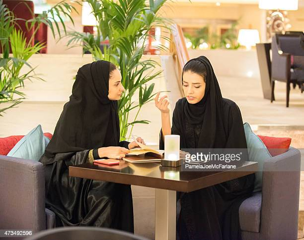 Middle Eastern Women Looking at Menu in Luxury Hotel Café